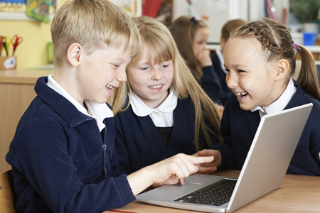 collaborating: Group Of Elementary School Children Working Together In Computer Class