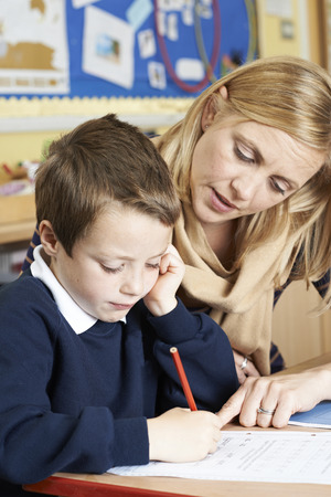 Teacher With Male Elementary School Pupil With Problem Standard-Bild