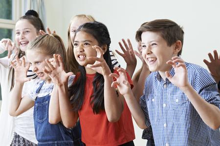 niños actuando: Grupo de niños que disfrutan de Club de Drama Juntos
