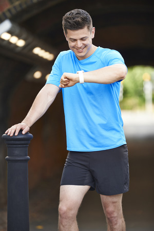 whilst: Man Looking At Activity Tracker Whilst Exercising In Urban Setting Stock Photo