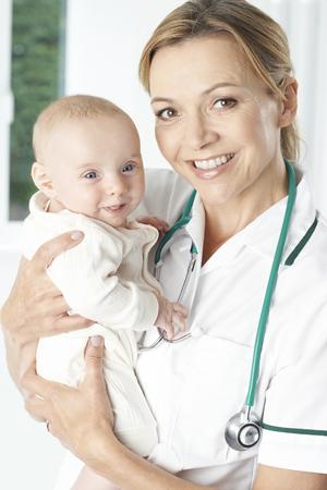 visitador medico: Portrait Of Nurse Holding Baby Girl