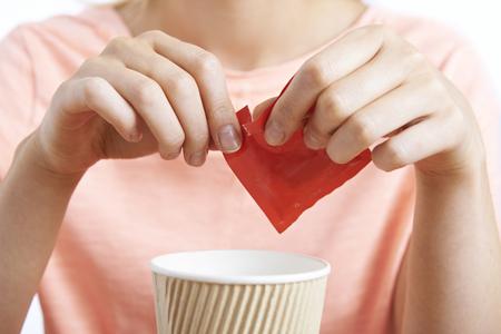 Woman Adding Artificial Sweetener To Coffee
