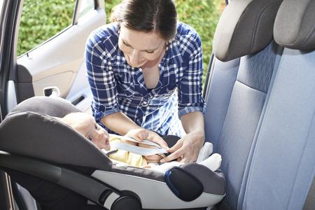 asiento coche: Poner de la madre del asiento del bebé en el coche para el viaje Foto de archivo