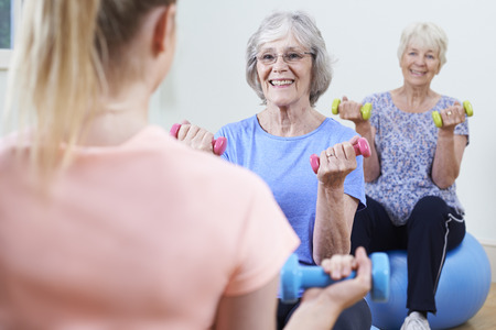 senior exercising: Senior Women At Fitness Class With Instructor Stock Photo