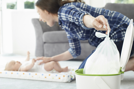 nappy: Mother Disposing Of Baby Nappy In Bin Stock Photo