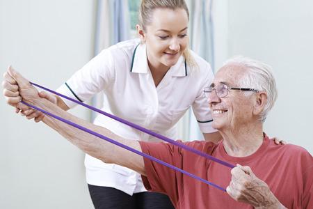 senior men: Physiotherapist Helping Senior Male To Use Resistance Band