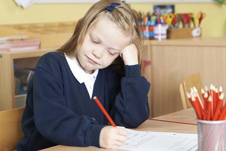 Bored Female Elementary School Pupil At Desk Stock Photo