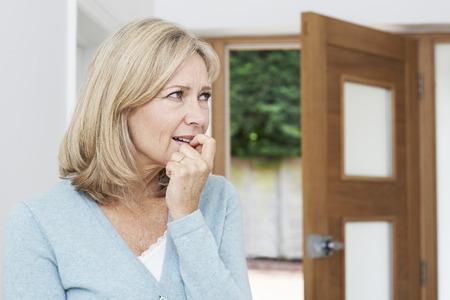 Droevige rijpe vrouw die lijdt aan agorafobie kijkt uit het Open Deur Stockfoto