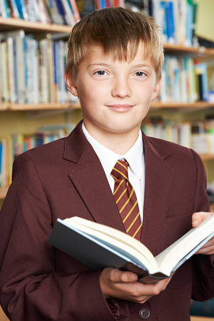 age old: Boy Wearing School Uniform Reading Book In Library Stock Photo
