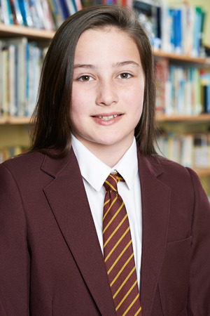school classroom: Female Pupil Wearing School Uniform Standing In Library