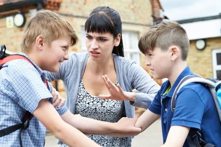 Leraar stoppen Twee jongens Vechten In Playground Stockfoto