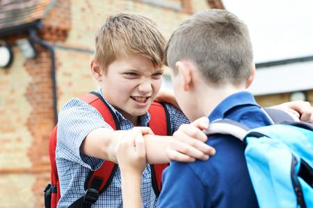 conflicto: Dos muchachos que luchan en patio de la escuela