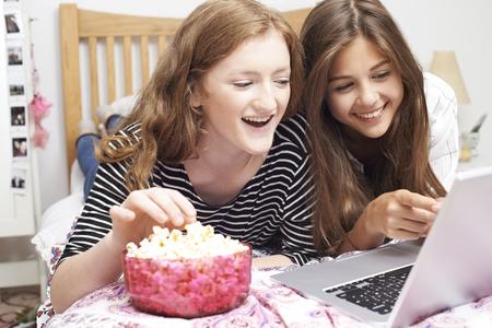 chicas adolescentes: Dos adolescentes que miran película en la computadora portátil en dormitorio Foto de archivo
