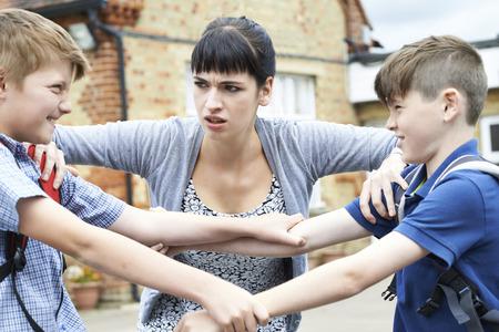 Profesor deteniendo a dos niños peleando en el patio de recreo