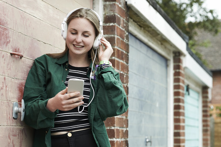 18 year old: Teenage Girl Wearing Headphones And Listening To Music In Urban Setting