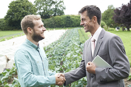 growing partnership: Farmer And Businessman Shaking Hands