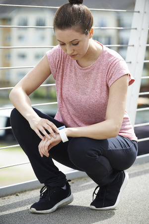 whilst: Woman Looking At Activity Tracker Whilst Exercising In City Stock Photo