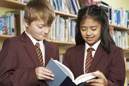 uniformes: Los alumnos portaban el uniforme de la escuela del libro de lectura en biblioteca Foto de archivo