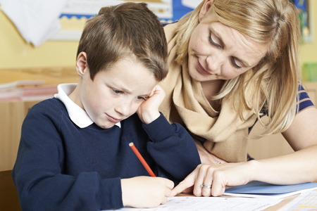 Teacher With Male Elementary School Pupil With Problem Stock Photo