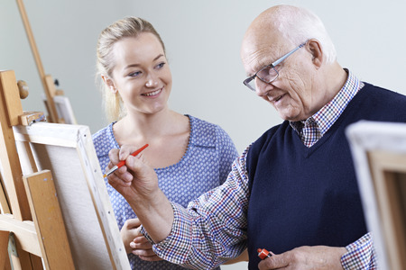 Senior Man Attending Painting Class With Teacher Stock Photo
