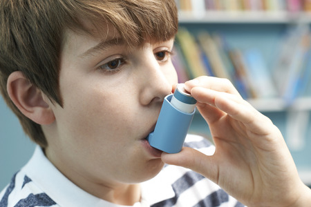 Boy Using Inhaler To Treat Asthma Attack