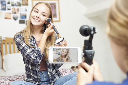 Two Teenage Girls Recording Beauty Blog In Bedroom Stock fotó - 65616471
