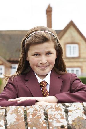 Portrait Of Girl In Uniform Outside School Building Stock Photo