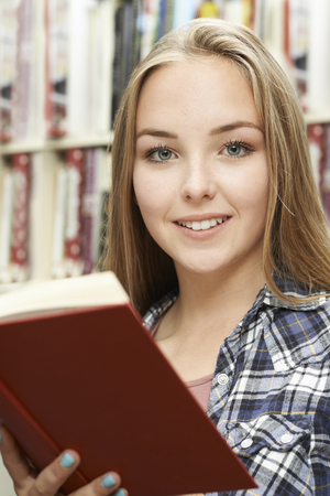 old books: Teenage Girl Reading Book At Home Stock Photo
