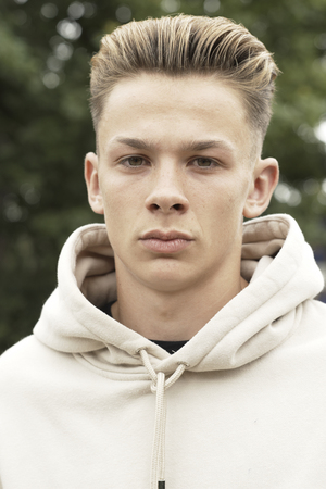 casual hooded top: Head And Shoulders Portrait Of Serious Teenage Boy