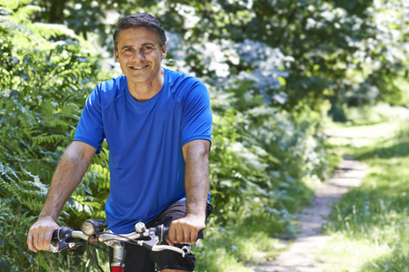 healthy men: Mature Man Cycling Along Path In Countryside