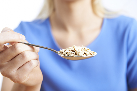 unrecognisable person: Close Up Of Woman With Oats On Spoon Stock Photo
