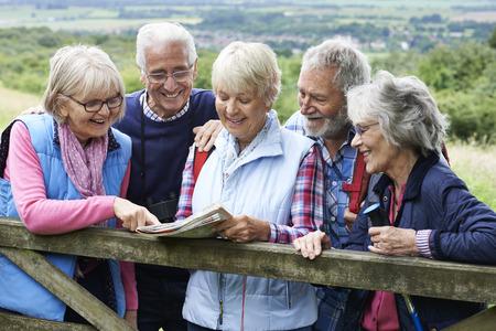 Groep hogere vrienden Wandelen In Platteland Stockfoto