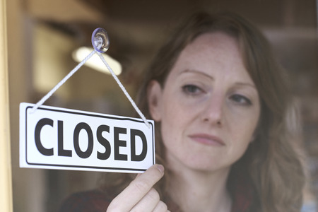 Store Owner Turning Closed Sign In Shop Doorway Archivio Fotografico