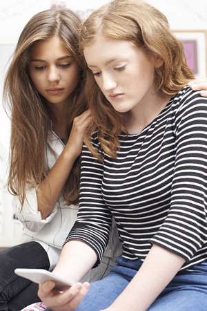 Teenage Girl With Friend Being Bullied By Text Message