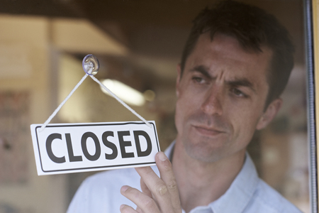 closed: Store Owner Turning Closed Sign In Shop Doorway Stock Photo