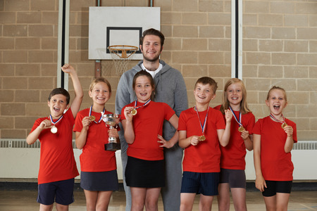 school sports: Victorious School Sports Team With Medals And Trophy In Gym