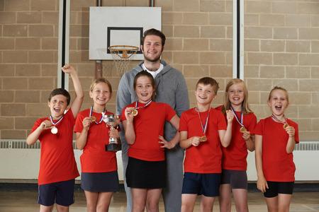 Victorious Schulsport-Team mit Medaillen und Trophy In Gym