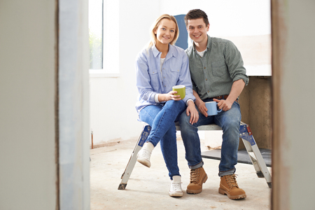 rennovation: Portrait Of Couple Sitting In Property Being Rennovated
