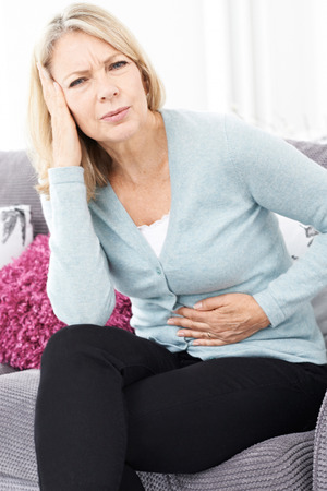 ibs: Mature Woman Suffering From Stomach Pain And Headache