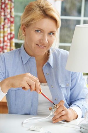 electrical plug: Woman Wiring Electrical Plug On Lamp At Home