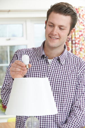 energy use: Man Putting Low Energy LED Lightbulb Into Lamp At Home