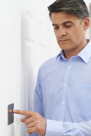 turning off: Mature Man Turning Off Light Switch At Home