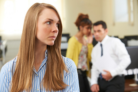Businesswoman Being Gossiped About By Colleagues In Office Banque d'images