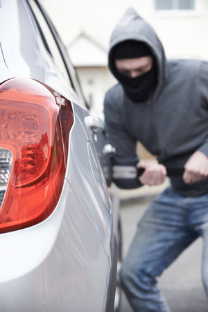 antisocial: Masked Man Breaking Into Car With Crowbar Stock Photo