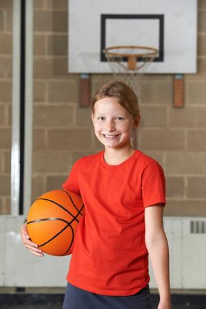 baloncesto chica: Retrato de la muchacha de la explotación agrícola de baloncesto de la escuela de gimnasia