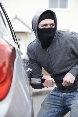 breaking: Masked Man Breaking Into Car With Crowbar Stock Photo