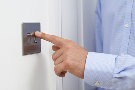 turning off: Close Up Of Man Turning Off Light Switch
