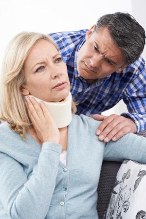 neck injury: Husband Comforting Husband Suffering With Neck Injury