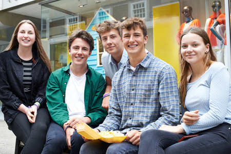 out of town: Portrait Of Teenage Friends Hanging Out In Town Together Eating Takeaway Food
