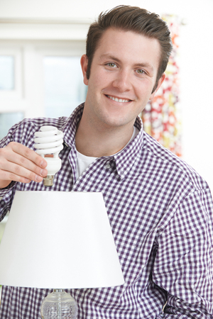 energy use: Man Putting Low Energy Lightbulb Into Lamp At Home Stock Photo
